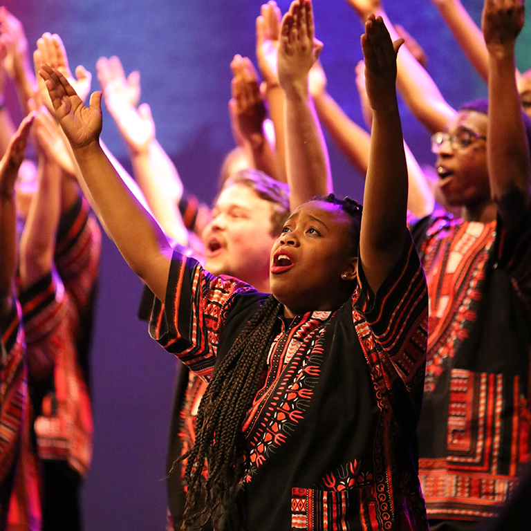Photo of a female vocalist with her arms raised in the African American Choral Ensemble.