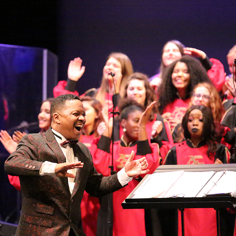Photo of Dr. Raymond Wise directing the African American Choral Ensemble during a concert.