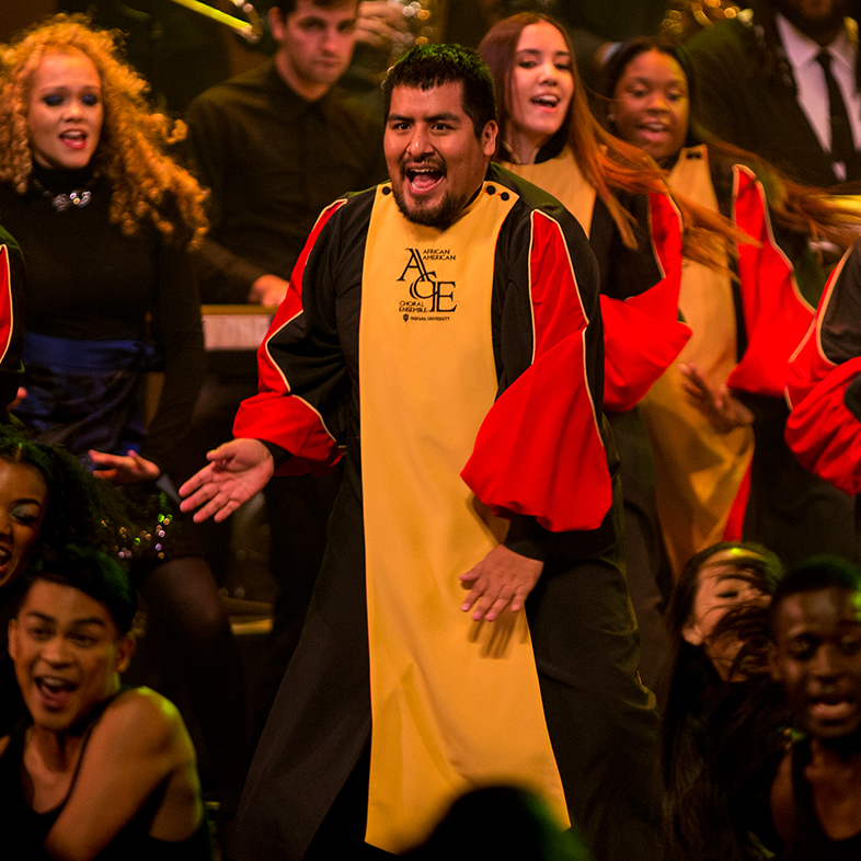 Photo of a male vocalist wearing a yellow choir robe in the African American Choral Ensemble.