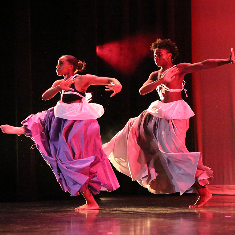 Photo of two dancers in the African American Dance Company jump in unison during a performance.