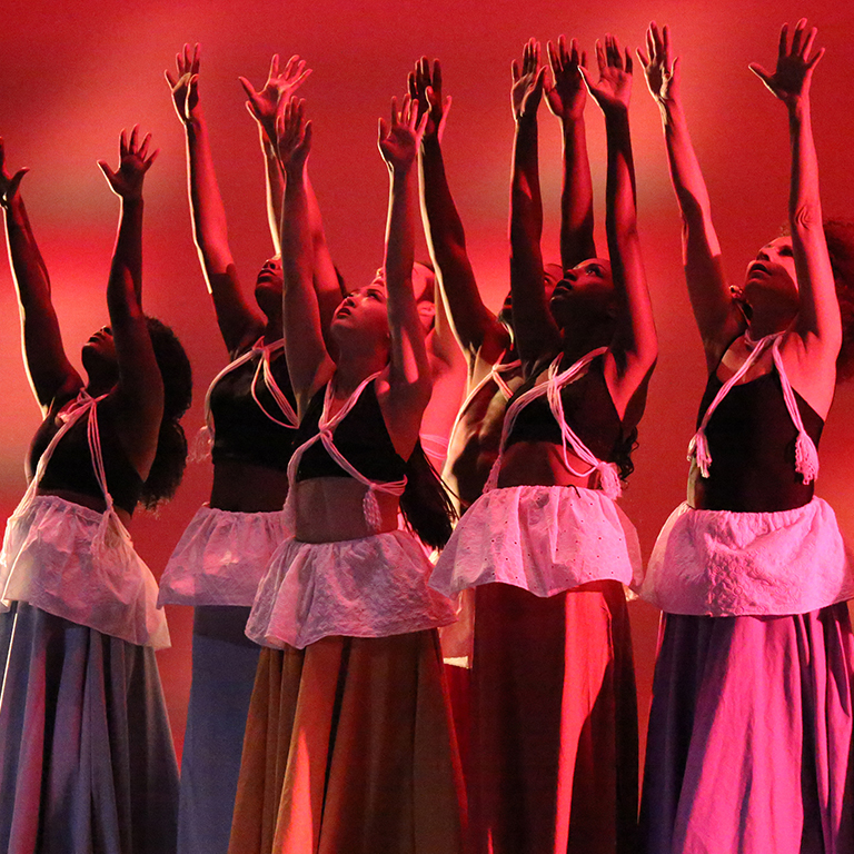 Photo of a group of dancers reaching their arms up during an African American Dance Company concert.
