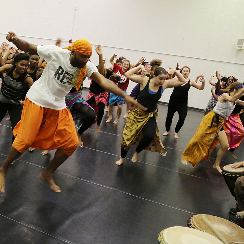 Photo of a group of dancers extending their arms toward drummers in a dance class.