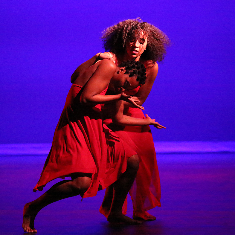 Photo of two female dancers performing during an African American Dance Company concert.