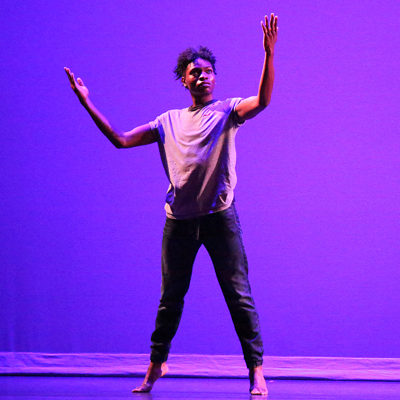 Photo of a male dancer on his toes during an African American Dance Company concert.