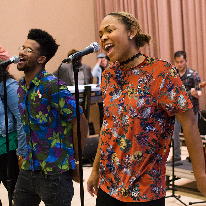 Photo of students singing into microphones and playing instruments during an IU Soul Revue rehearsal in the Neal-Marshall Black Culture Center.
