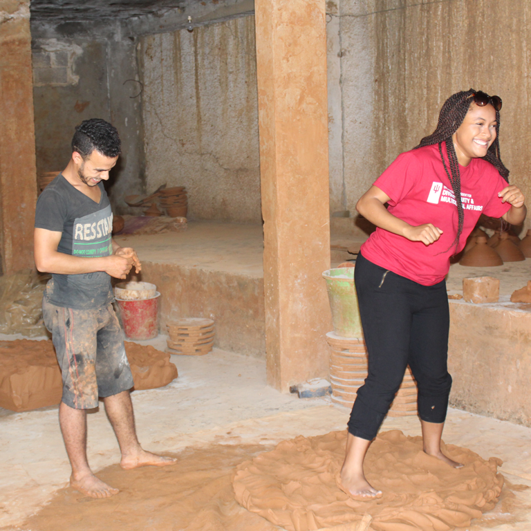 Mica Caine playfully stomps wet clay during her study abroad experience in Morocco.