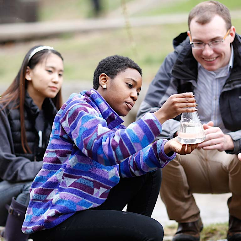 Student look at a beaker while holding class outside.