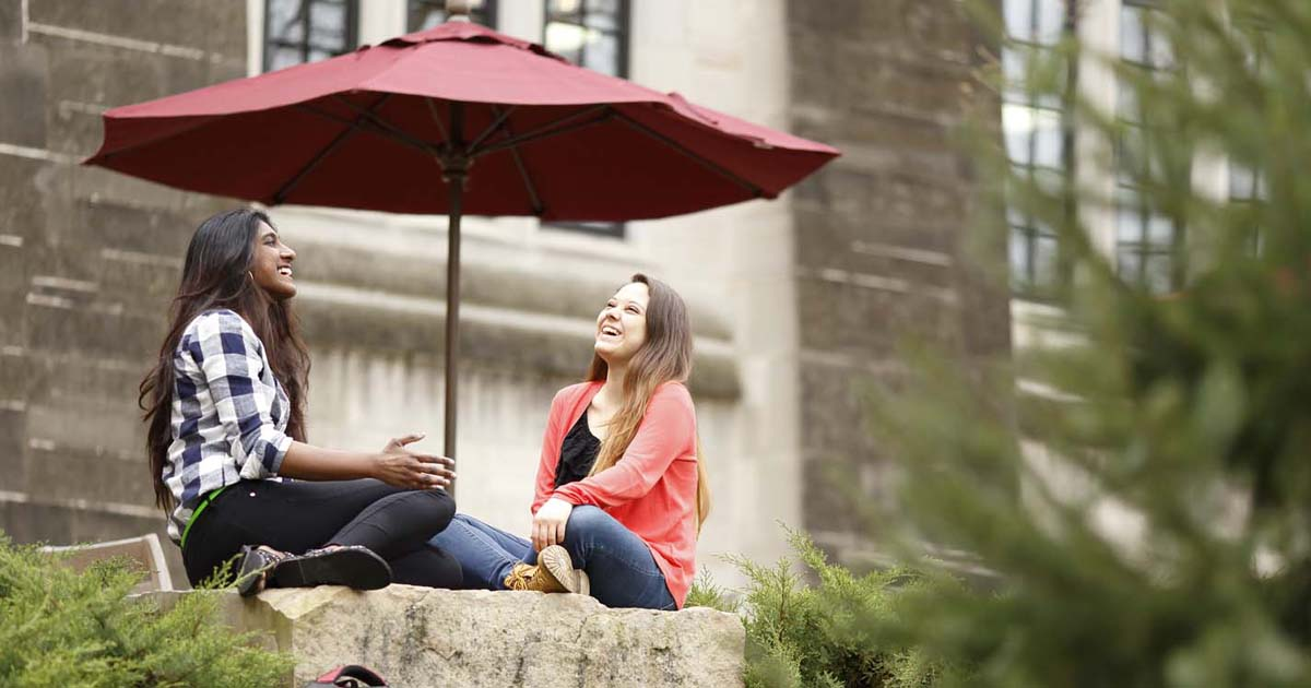 Two students sit and laugh together in front of a campus building.