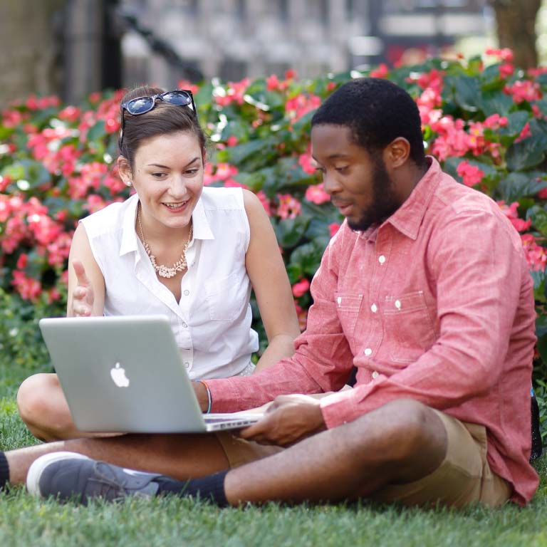 Students discuss and look at a laptop while sitting in the grass on campus.