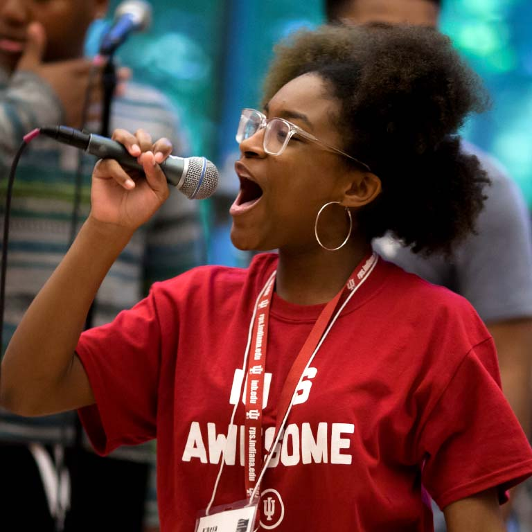An IU student sings in a microphone.
