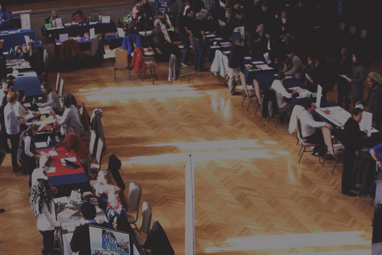 Indoor aerial view of career fair attendees interacting with table booths.