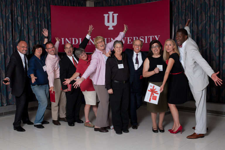 Group of people posing in front of an IU banner laughing and smiling.