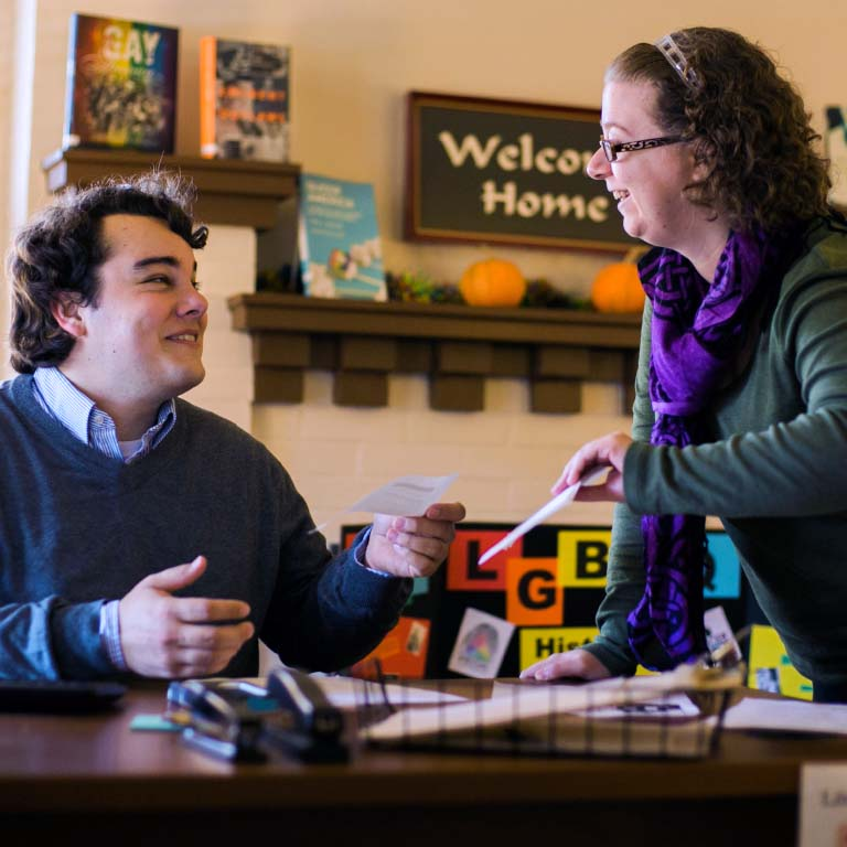 A LGBTQ+ Culture Center representative hands a student information.
