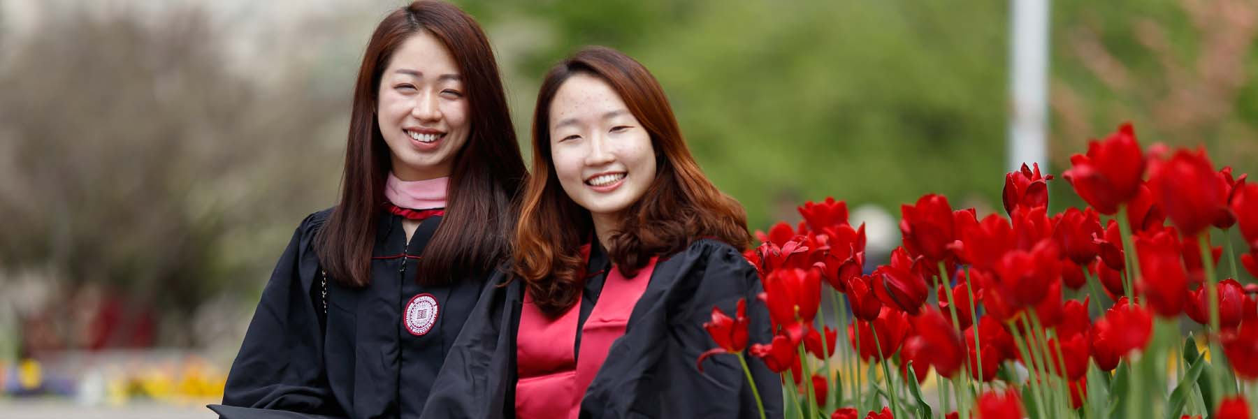 Two girls embrace while wearing their IU graduation gowns.