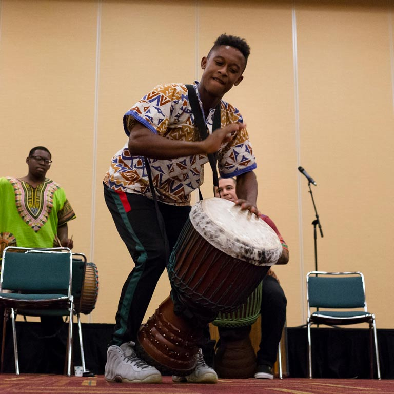 A young man in a colorful shirt beats on a drum.