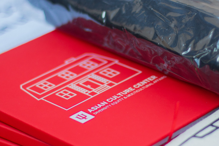 Red notebook with a stencil of the ACC house and the words Asian Culture Center