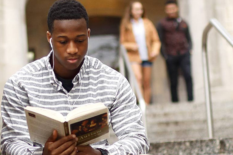 Young black male sitting on steps reading a book.