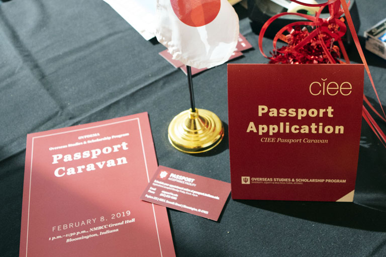 Passport Caravan brochure, business card, and table tent arranged on black table cloth