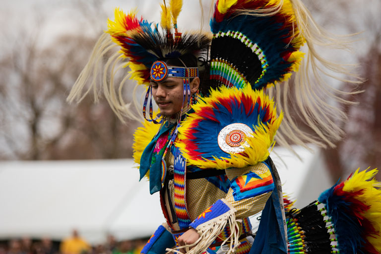 Male in traditional first nations powwow yellow attire dancing.