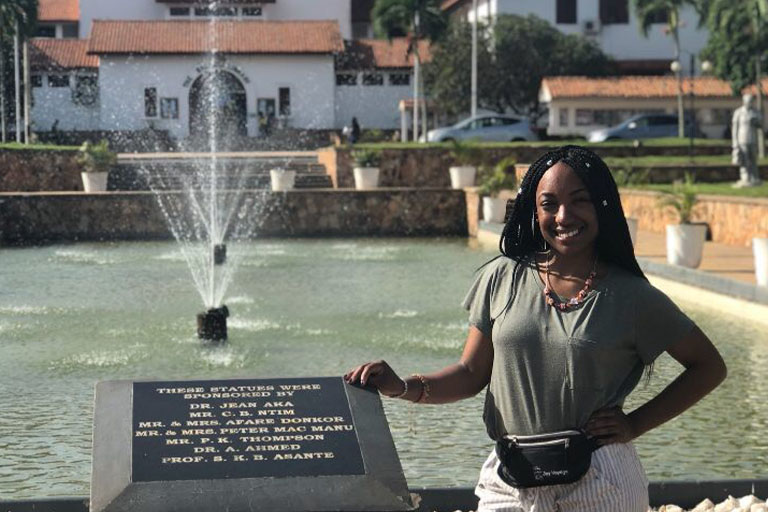 African American female standing by signage, plaque in front of a water feature during study abroad trip.