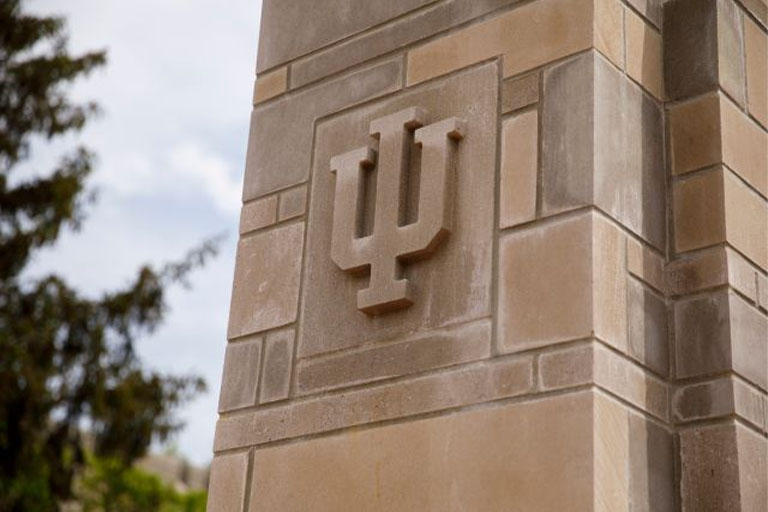A limestone IU trident adorns a gate outside the Indiana Memorial Union on a summer day at IU Bloomington on Friday, May 17, 2019.