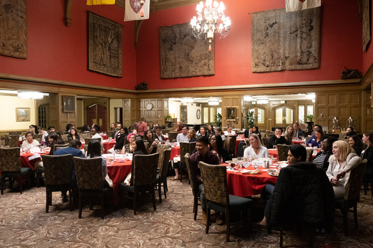 Photo of Dinner Symposium attendees seated at tables in IMU Tudor Room listening to panelist speak.