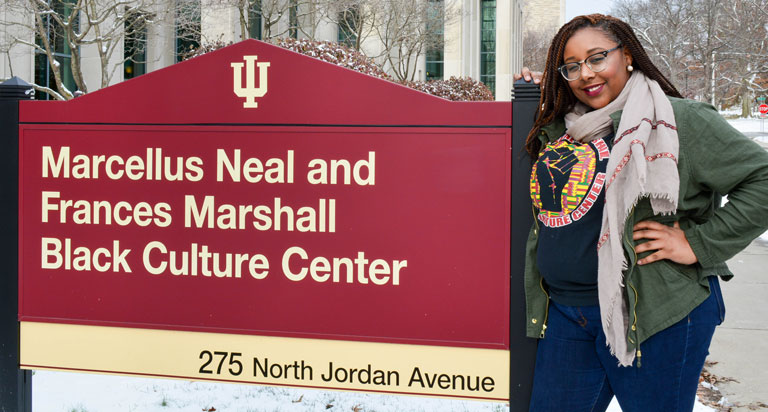 Lauren Blackwell stands next to the Neal-Marshall Black Culture Center sign.