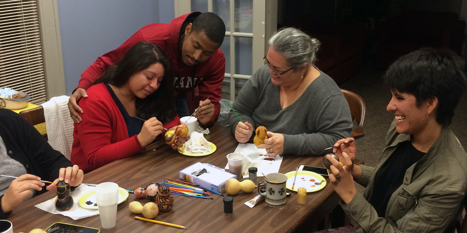A student helps a participant paint during La Casa's Wellness and Culture Talking Circle series.