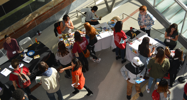 Aerial view of student visiting information tables at the OVPDEMA Study Abroad Fair.