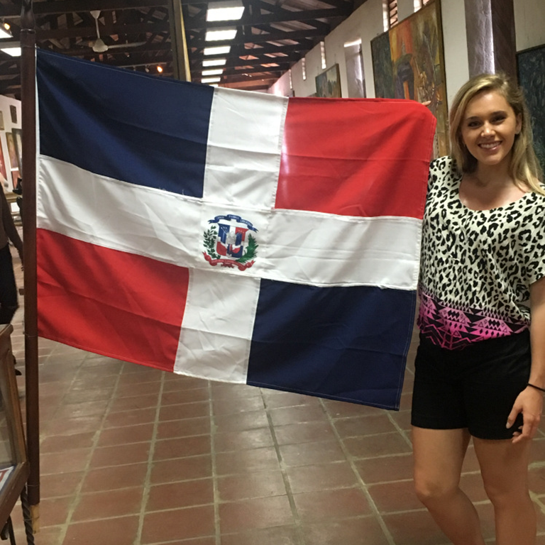 Alyssa Claymiller holds a flag from Santo Domingo.