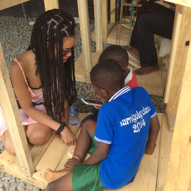 Toni Pringley kneels with a child during her overseas study in Ghana.